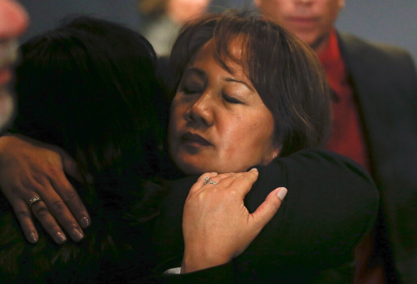 Trudy Raymundo, head of the San Bernardino County Department of Public Health, gets a hug immediately after a news conference as county offices reopened.