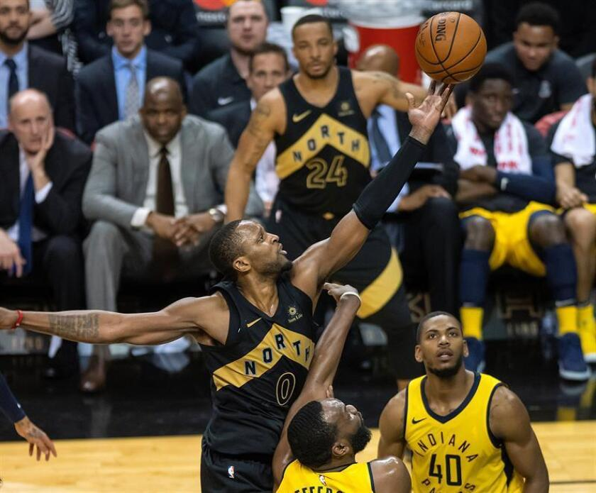Toronto Raptors forward Calvin CJ Miles (L) throws to the basket over Indiana Pacers guard Glenn Robinson (R) and center Al Jefferson (bottom) in the fourth quarter of their NBA basketball game in Toronto, Canada, 06 April 2018. The Raptors defeated the Pacers. (Baloncesto) EFE