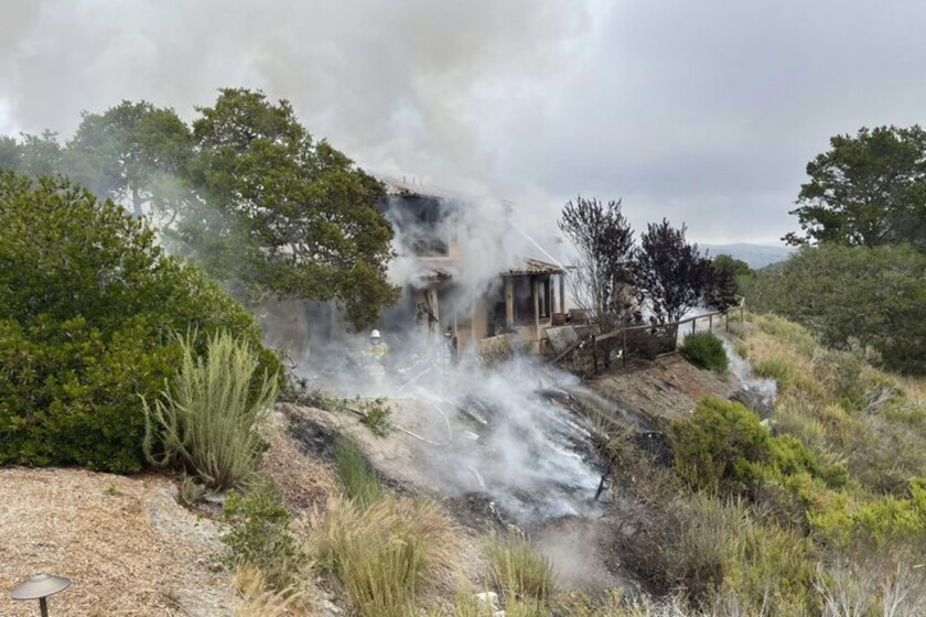 In this photo provided by the Monterey County Regional Fire District is the scene where a plane crashed into a home near Highway 68 in Monterey County, Calif., on Tuesday, July 13, 2021. A small plane crashed into a home starting a fire in the house that spread to nearby wild land. It is not yet known if people were inside the residence or how many people were on the plane, an official said. The twin-engine Cessna 421 crashed into a residential area after departing from the Monterey Regional Airport in Monterey, Calif. (Monterey County Regional Fire District via AP)