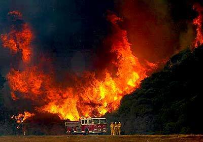 Firefighters take a stance as flames threaten to cross Interstate 15 near Devore.