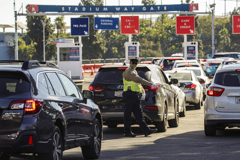 An officer directs traffic as residents queue up for COVID-19 tests at Dodger Stadium in Los Angeles.