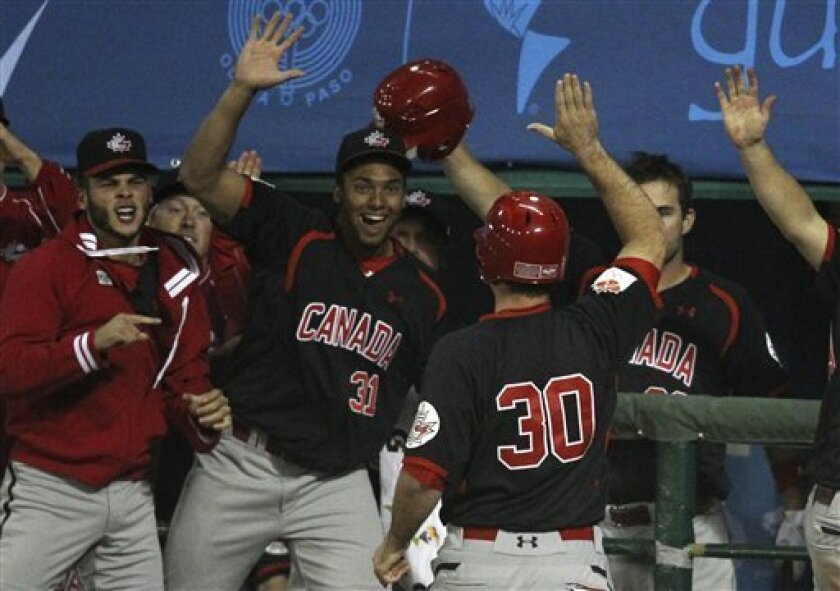 Canada designated hitter Chris Robinson (30) high fives with teammates after scoring during the sixth inning of the final baseball game against the United States at the Pan American Games in Lagos de Moreno, Mexico, Tuesday Oct. 25, 2011. (AP Photo/Javier Galeano)