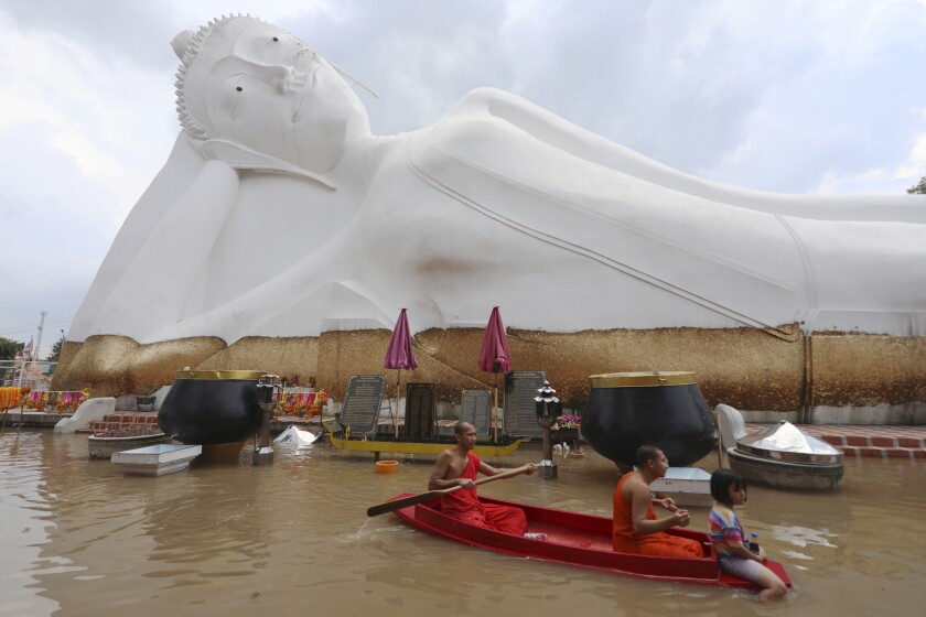 Buddhist monks paddle a boat through floodwaters in front of a reclining Buddha at the Wat Satue in Ayutthaya province north of Bangkok, Thailand, Monday, Oct. 4, 2021. Officials in Thailand expressed optimism Monday that widespread flooding is easing, with signs that the capital, Bangkok, may be spared serious damage. (AP Photo/Nathathida Adireksarn)