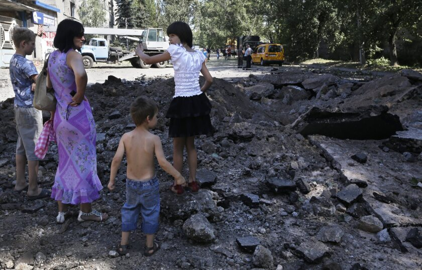 As shelling and gunfire exchanges between Ukrainian troops and pro-Russia gunmen close in on Donetsk, as in this residential area on Wednesday, concerns are mounting that Russian President Vladimir Putin might invade Ukraine under the pretext of aiding the Russian-speaking communities.