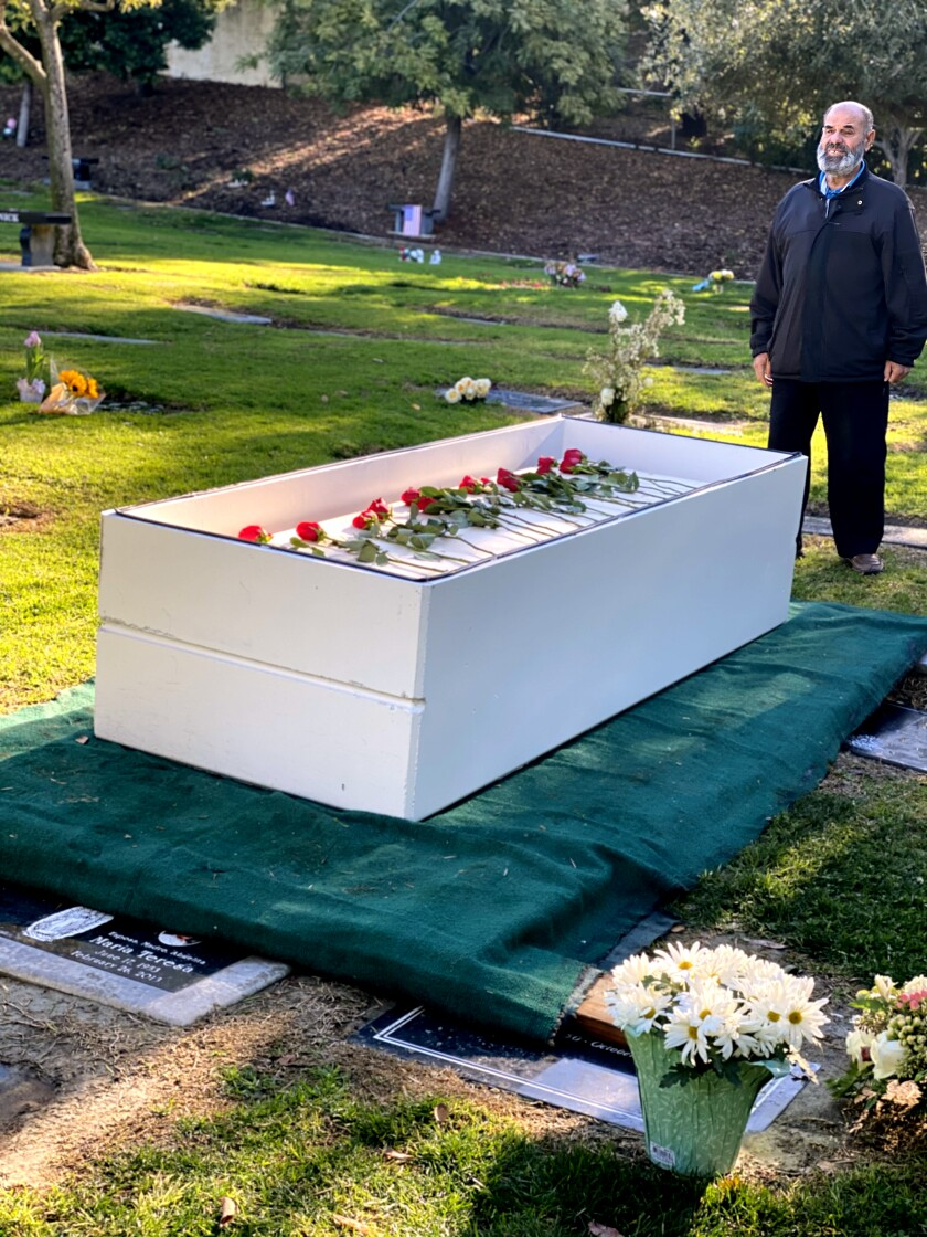 A man stands over a coffin at a graveyard