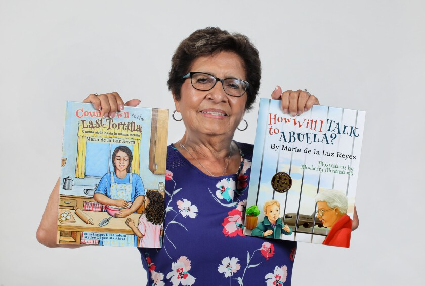 San Marcos author Maria de la Luz Reyes with two of her children's books.