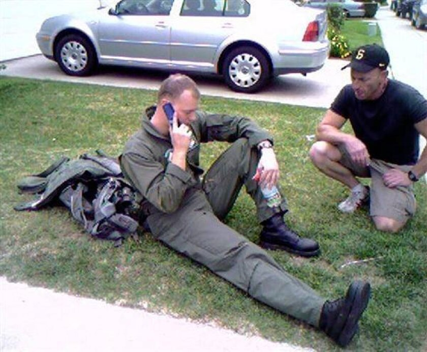 Lt. Dan Neubauer sits on the lawn of a house after ejecting from the F/A-18D that crashed in University City.