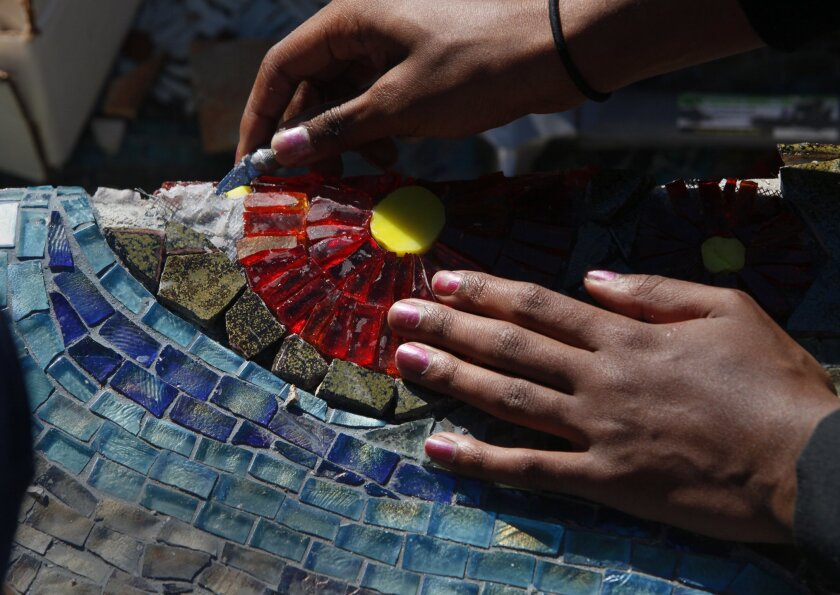 Coronado High student Kendall Cromartie, 15, carefully touches up a mosaic that students are creating on campus.