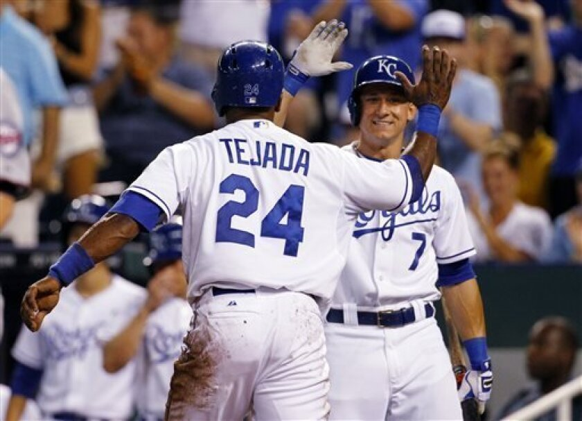 Kansas City Royals' Miguel Tejada (24) is congratulated by David Lough (7) after scoring off of an Alcides Escobar single in the fourth inning of a baseball game against the Minnesota Twins at Kauffman Stadium in Kansas City, Mo., Wednesday, Aug. 7, 2013. (AP Photo/Colin E. Braley)