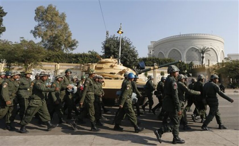 """Soldiers walk past a military tank securing the presidential palace in Cairo, Egypt, Thursday, Dec. 13, 2012. Egypt's opposition called on its followers to vote """"no"""" in a crucial referendum on a disputed constitution drafted by Islamist supporters of President Mohammed Morsi. (AP Photo/Petr David Josek)"""