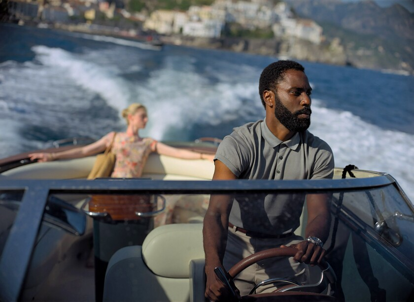 "Elizabeth Debicki and John David Washington ride in a speedboat in the movie ""Tenet"""