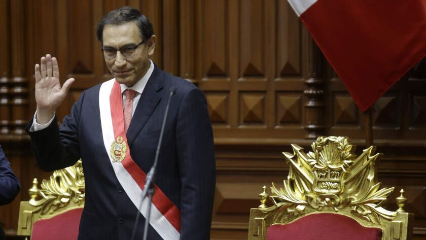 Peruvian President Martin Vizcarra waves after being sworn into office in Lima, Peru, on Friday. His predecessor, Pedro Pablo Kuczynski, resigned over corruption allegations.