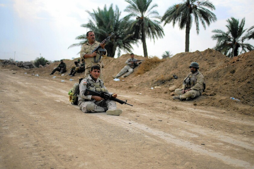 Iraqi soldiers keep watch in Jarf Sakhr, southwest of Baghdad, last month. The U.S. military witnessed Iraqi army shortcomings as long ago as 2003, when even soldiers in the elite Republican Guard deserted.