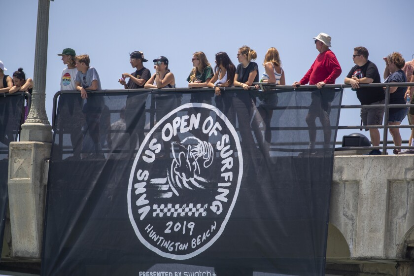 """People stand behind a railing where a flag is hung that says """"Vans U.S. Open of Surfing."""""""