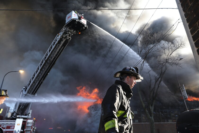 """Firefighters work to extinguish a fire at a commercial building on Thursday, Dec. 10, 2020, in Chicago. Chicago Fire Department spokesman Larry Merritt says crews were called to flames shooting through the roof of Best Value Auto Body Supply Inc. He says the damage is """"extensive"""" and the building most likely will be demolished. (Antonio Perez/Chicago Tribune via AP)"""