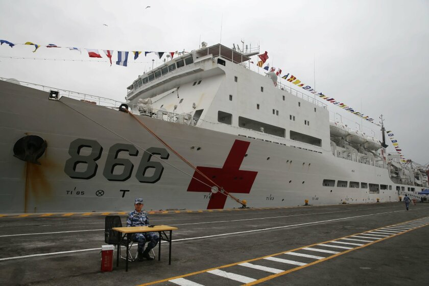 "A Chinese official sits in front of Chinese naval hospital ship in the port of Callao, Peru, Tuesday, Dec. 22, 2015. The Peace Ark, a Chinese naval hospital ship is making a first-ever call into a South American port in a sign of the Asian economic giant's growing influence in Washington's backyard. It's the last destination on a three-month ""Harmonious Mission"" that also included stops in Australia, Mexico and the U.S. (AP Photo/Martin Mejia)"