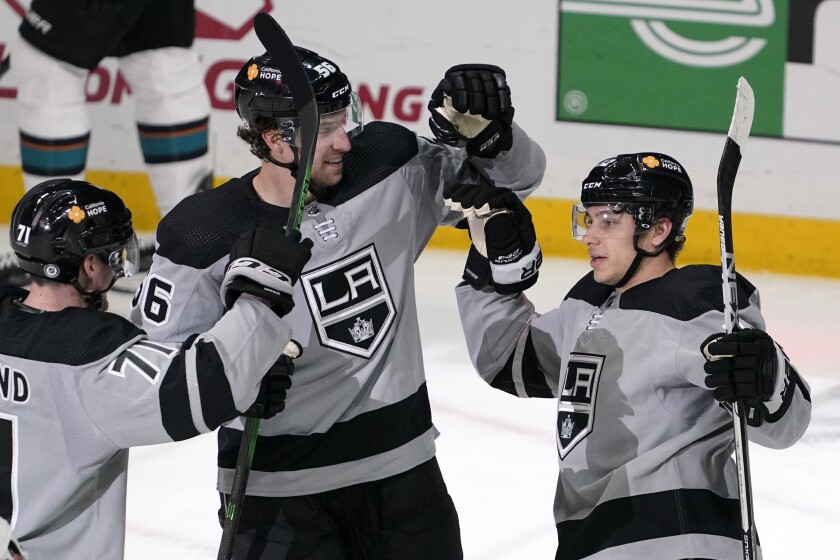 Los Angeles Kings center Trevor Moore, right, celebrates his goal with defenseman Austin Strand, left, and defenseman Kurtis MacDermid during the second period of an NHL hockey game against the San Jose Sharks Saturday, April 3, 2021, in Los Angeles. (AP Photo/Mark J. Terrill)