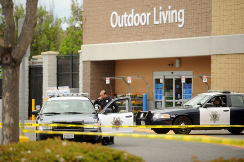 Police cars maintain a perimeter around a San Jose Walmart after a motorist drove through a store entrance and began assaulting shoppers.