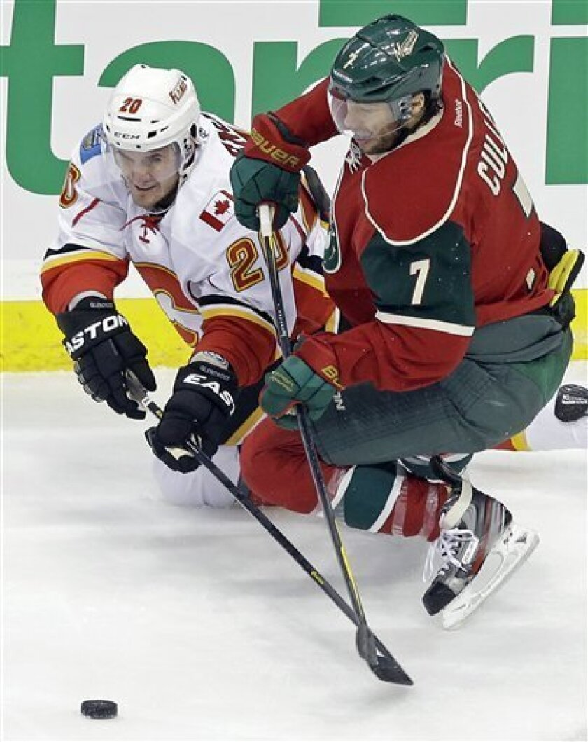 Calgary Flames' Curtis Glencross, left, and Minnesota Wild's Matt Cullen reach for the loose puck in the first period of an NHL hockey game Tuesday, Feb. 26, 2013, in St. Paul, Minn. (AP Photo/Jim Mone)