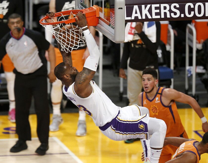 Lakers forward LeBron James hangs on the rim after throwing down a dunk off an alley-oop from Alex Caruso.