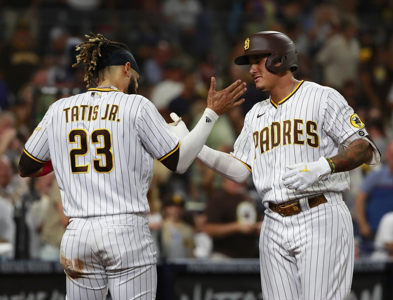 SAN DIEGO, CA - SEPTEMBER 21: San Diego Padres' Manny Machado celebrates with Fernando Tatis Jr. after hitting a home run in the third inning against the San Francisco Giants at Petco Park on Tuesday, Sept. 21, 2021 in San Diego, CA. (K.C. Alfred / The San Diego Union-Tribune)