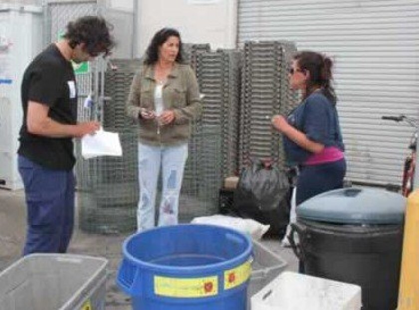 tresha Souza (center) speaks with some of the regular customers at her Pacific Beach recycling center last month.