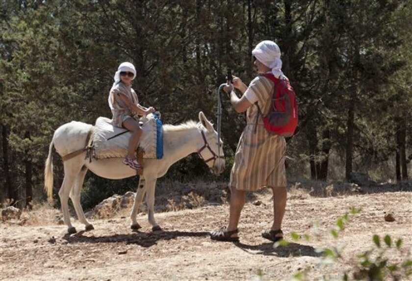 American tourist Peter Scherr uses a smartphone to send a photograph of his daughter using a Wi-Fi router placed on a donkey Kfar Kedem, a biblical reenactment park in the village of Hoshaya in the Galilee, northern Israel, Wednesday, Aug. 22, 2012. Visitors riding donkeys through the Old Testament
