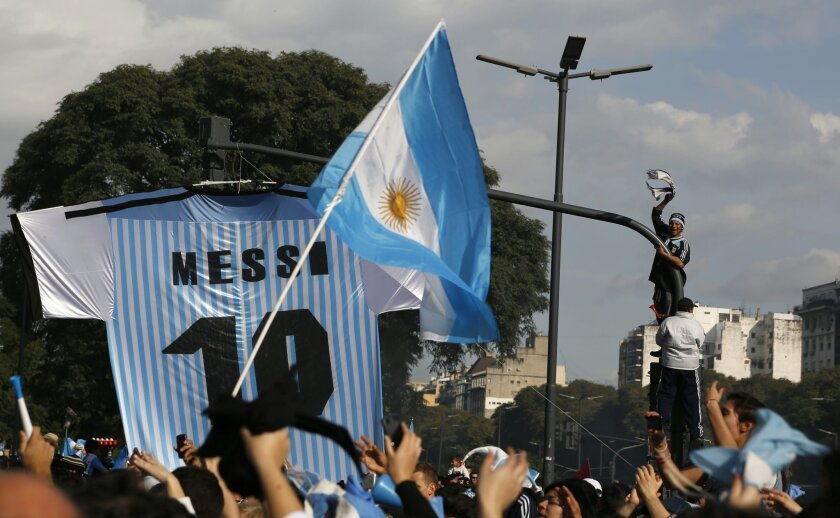 Soccer fans gather at the obelisk to welcome home Argentina's soccer team, before it was announced that the team won't be coming to this landmark for a welcome ceremony after they landed at the airport in Buenos Aires, Argentina, Monday, July 14, 2014. Fans came out to welcome home Argentina's team after it was defeated 1-0 by Germany at the Brazil World Cup final match on Sunday. (AP Photo/Jorge Saenz)