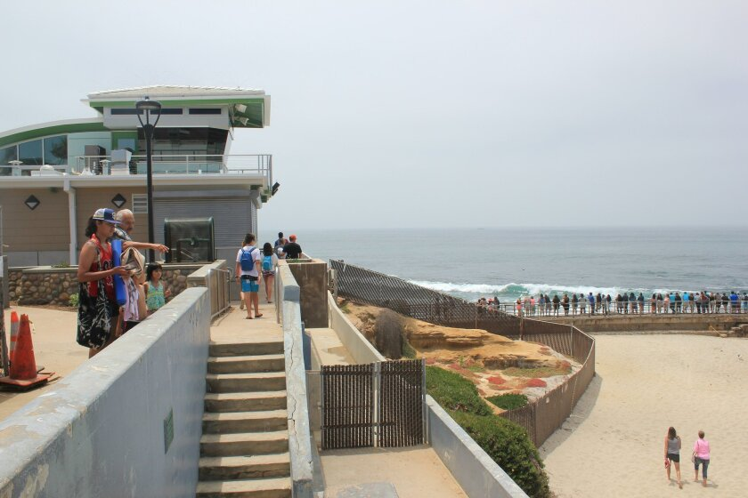 Tourists explore the area around the lifeguard tower, June 27.