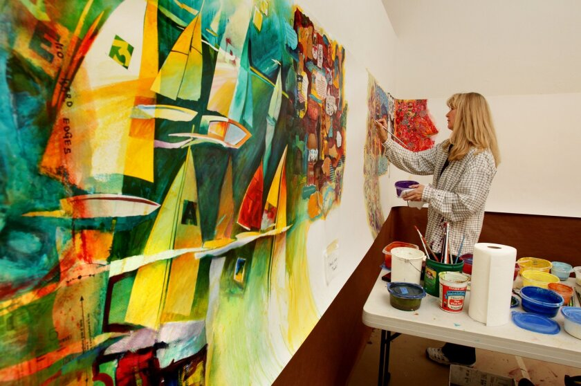 """Artist Lucinda Hayes works on her section of the """"Artful Inches"""" project last week in a studio at the Escondido Municipal Gallery. Paintings by other artists are to her left. The fundraiser will benefit high school artists."""