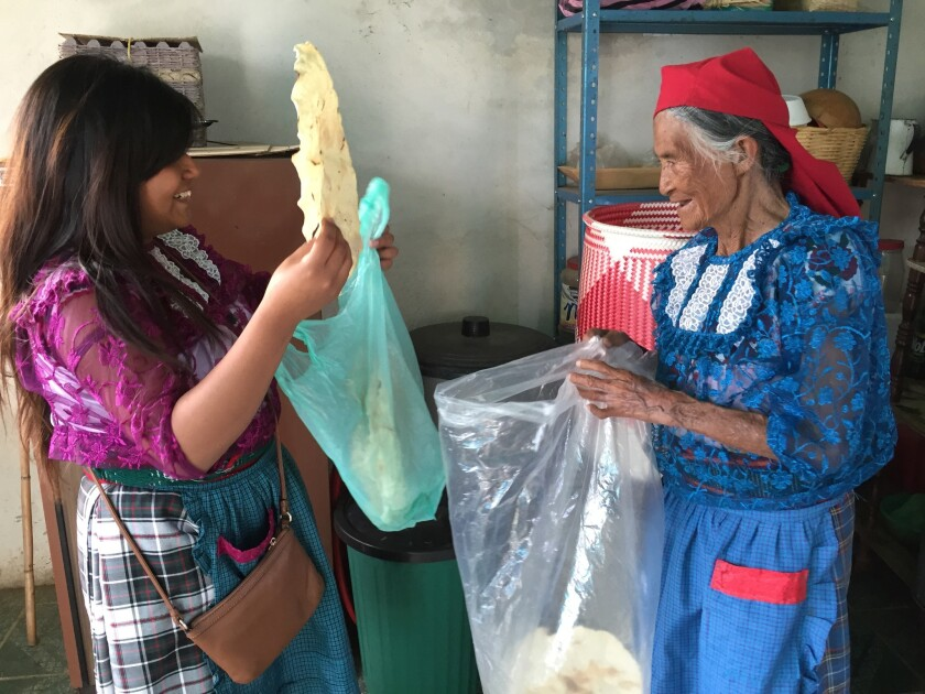 Veronica Martinez Sanchez helps her grandmother Sofia Gomez pack up freshly made Oaxacan-style tortillas. Martinez and Gomez spent most mornings in the kitchen, catching up over freshly brewed coffee and eggs.