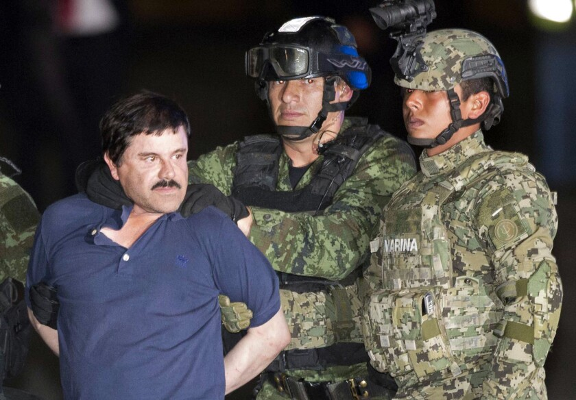 "Drug lord Joaquin ""El Chapo"" Guzman is made to face the press as he is escorted to a helicopter in handcuffs in Mexico City after his recapture in January."