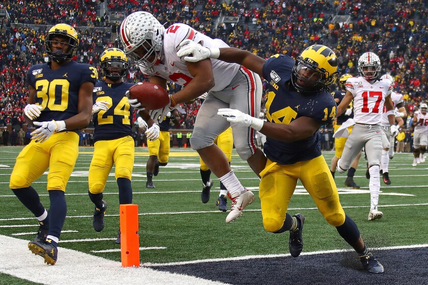 Ohio State running back J.K. Dobbins dives into the end zone ahead of Michigan defensive back Josh Metellus.