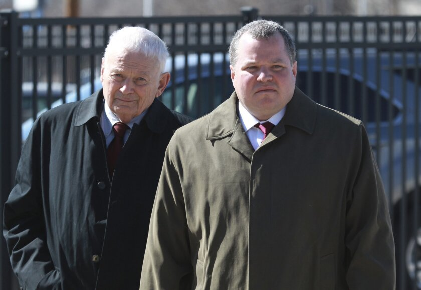 Former St. Clair County Judge Michael Cook, right, arrives at the U.S. District Courthouse in East St. Louis, Ill., with his father, Bruce Cook. U.S. District Judge Joe Billy McDade on Wednesday rejected a plea deal on heroin and gun charges for the former Illinois judge at the center of a courthouse drug scandal, saying the 18-month prison sentence wasn't long enough. Cook, 43, who has been free on bond, pleaded guilty in November to a misdemeanor heroin-possession charge and a felony count of having firearms while being a user of controlled substances. (AP Photo/Belleville News-Democrat, Derik Holtmann)