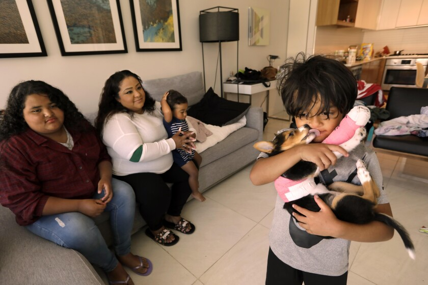 Natalie Quintanilla, and her children Victoria, 11, from left, Patrick, 1 1/2, and Mason, 5, holding the family dog Lassie.