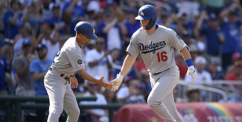 Dodgers catcher Will Smith is congratulated by third base coach Dino Ebel after hitting a home run against the Washington Nationals on Saturday.