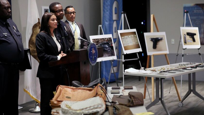 Stolen objects are displayed while Capt. Lillian Carranza, second from left, commanding officer of the Los Angeles Police Department's Commercial Crimes Division, shares details about arrests made in connection with recent burglaries at the homes of celebrities.