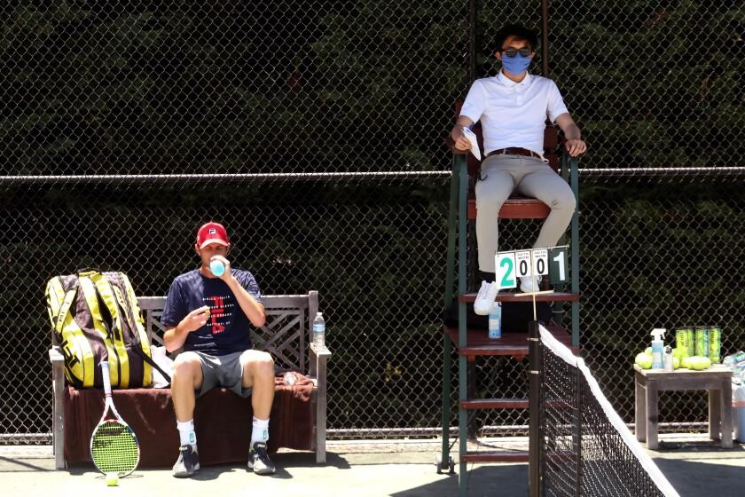 Sam Querrey, left, and umpire Albert Ton, masked.