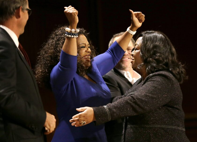 Actor, talk show host and philanthropist Oprah Winfrey, center left, and television producer and writer Shonda Rhimes, right, embrace on stage during the W.E.B. Du Bois medal award ceremonies, Tuesday, Sept. 30, 2014, on the campus of Harvard University, in Cambridge, Mass. The Du Bois Medal is Har