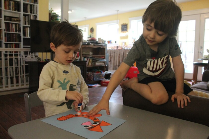 Two small boys use a glue stick to create an orange paper cat shaped like the letter C