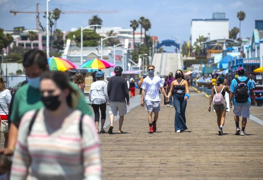 People in face masks walk on the Santa Monica Pier