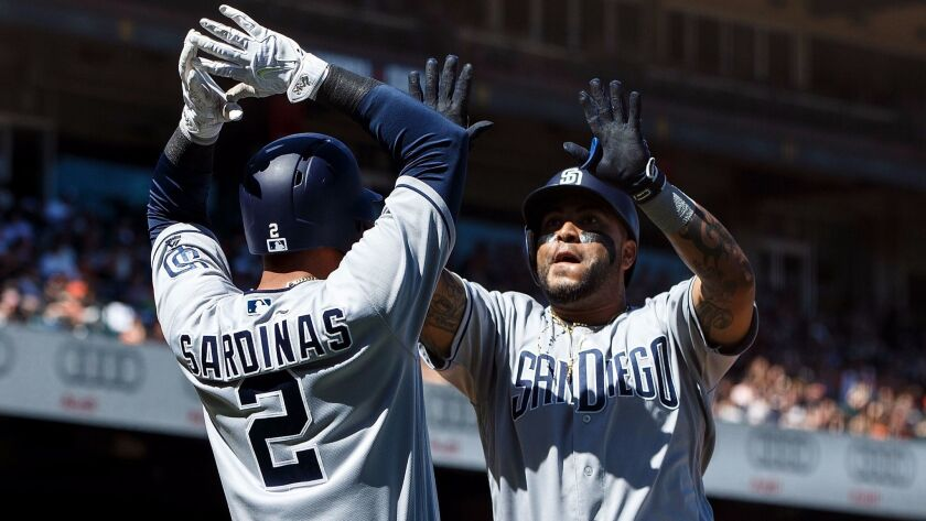 Hector Sanchez of the San Diego Padres is congratulated by Luis Sardinas after hitting a two-run home run against the San Francisco Giants during the ninth inning at AT&T Park on April 30, 201,7 in San Francisco, California.