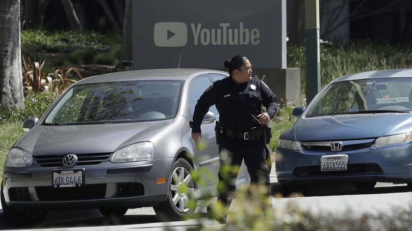 An officer runs past a YouTube sign near the company's complex in San Bruno, Calif., on Tuesday.