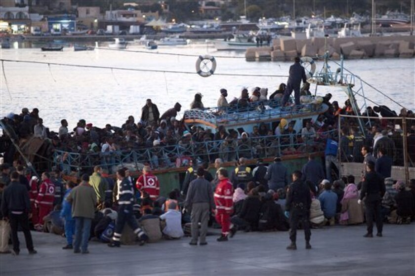 Immigrants disembark a boat at Lampedusa's harbor, Italy, Friday, April 8, 2011. After days of fierce sparring, Italy and France patched up their differences Friday over the fate of thousands of Tunisian migrants, avoiding a major rift over European Union border control rules. Top security officials from Italy and France sought a conciliatory tone as they struggled with the crush of more than 20,000 Tunisians who sailed on often rickety boats to Italy's southernmost point, the tiny Mediterranean island of Lampedusa. (AP Photo/Giorgos Moutafis) GREECE OUT