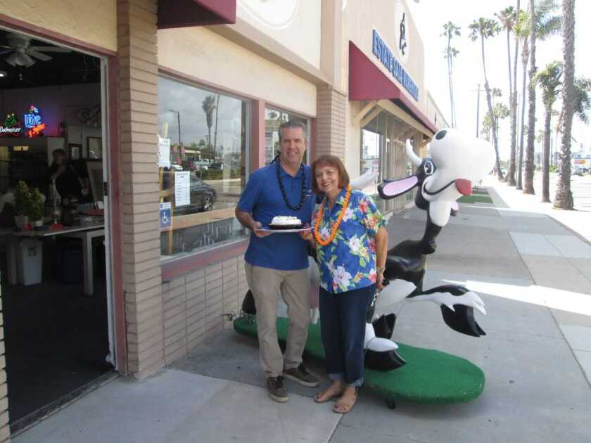 """Todd Stephenson, left, owner of Estate Warehouse in Oceanside, will lead a dessert auction at the Brother Benno's """"Ohana Luau."""" Linda Donahue, auxiliary co-chair, presents him with a pie. Brother Benno's Auxiliary will host a """"Ohana Luau"""" fundraiser from 5 to 8 p.m. on July 26 at the Rancho Calevero Mobilehome Park Clubhouse, 3570 Calevero Lane. The family-friendly event will feature a Hawaiian-style buffet and a dessert auction hosted by Todd Stephenson of Estate Warehouse. Music and dancing by the Sunset Strummers 'Ohana. Tickets are $30 for adults; $15 for children 7-12; free for ages 6 and under free. Raffle prizes. Proceeds will benefit the Brother Benno's Foundation which provides food, clothing, counseling and recovery homes for the homeless, military and low-income families. Tickets are at tinyurl.com/yxhodbpf. For questions, email congatime9@yahoo.com or auxiliary@brotherbenno.org."""