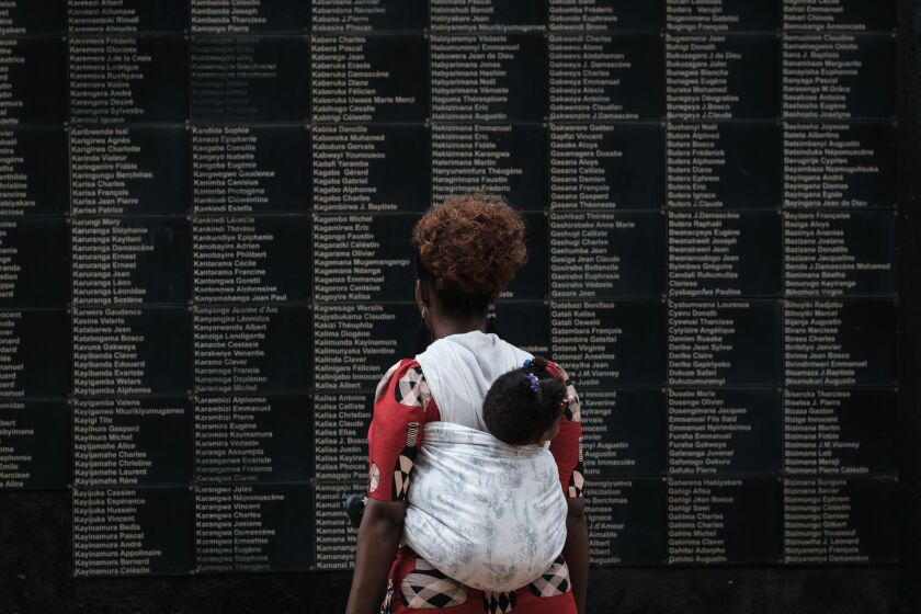 A woman visits the Kigali Genocide Memorial in Rwanda, which features a wall of victims' names.