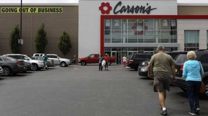 People walk out with bags of goods while others walk in to the Carson's store in Evergreen Park on Aug. 24, 2018, days before the store was set to close for good. The Carson's name may live on, as its parent company is selling its intellectual property to an undisclosed buyer.