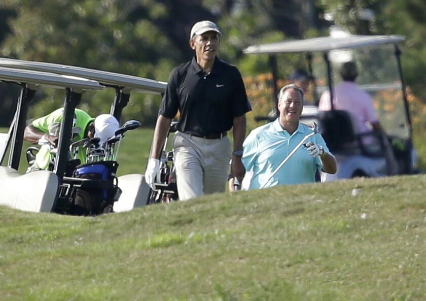 President Barack Obama, center, and golf partner Robert Wolf, right, walk toward a green while golfing at Farm Neck Golf Club, Sunday, Aug. 10, 2014, in Oak Bluffs, Mass., on the island of Martha's Vineyard. President Obama on Saturday left Washington for his familiar spot on Martha's Vineyard for a two-week summer vacation. (AP Photo/Steven Senne)