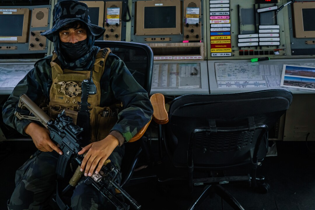 A fighter with a rifle sits inside an airport control tower