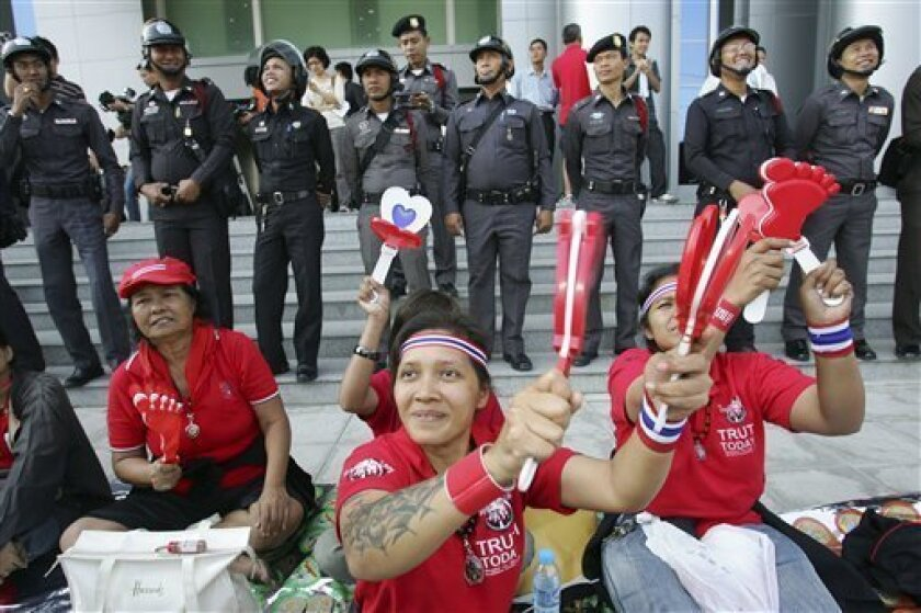 Pro-government demonstrator sit in front of the Administrative court in Bangkok on Tuesday Dec,2.2008. Hundreds of pro-government demonstrators swarmed around the court building forcing the relocation of judges who will rule on the fate of a Thai government beset by protests and a virtual shutdown of international air links. (AP Photo/Sakchai Lalit)